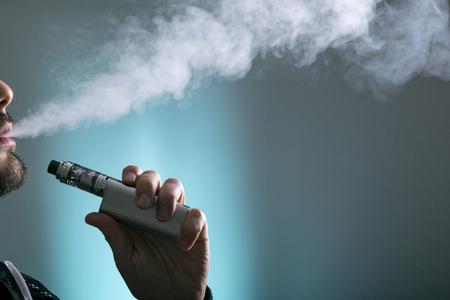junger Mann vape elektronische Zigarettenwolke, indem man einen Umb., Rauch Tricks des vaping Gerätehintergrundes verwendet.