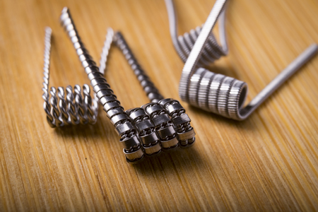 close up twisted coils for e cig or electronic cigarette for vape devices, RDA prebuild coil clapton over a wooden background. Stock Photo