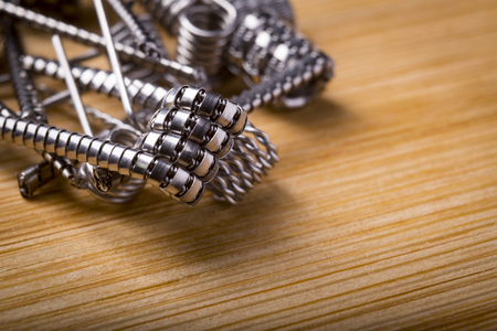 close up twisted coils for e cig or electronic cigarette for vape devices, RDA prebuild coil clapton over a wooden background. Imagens