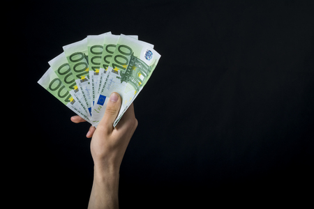 excited hand holding 100 euro money, hand holding one hundred euro cash isolated on a black background