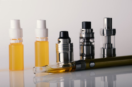 isolated vape tanks and e liquid for electronic cigarette or e cig over a white background. vaping rdta and e juice for vaping devices.  Stock Photo