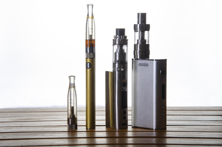 Popular vaping e cig devices mod and pen.electronic cigarette over a wood background. vaporizer e-cig old device model over a white background. Stock fotó