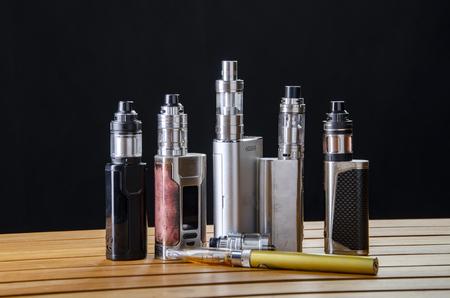 Popular vaping e cig devices mod.electronic cigarette over a black background. vaporizer e-cig old device model. pen cigarette