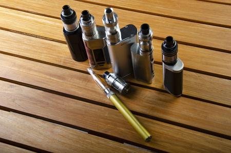 Popular vaping e cig devices mod.electronic cigarette over a wood background. vaporizer e-cig old device model.
