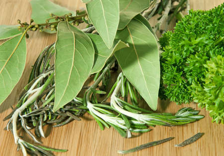 bay leaf: Parsley, rosemary and bay leaf on the cutting board. Stock Photo