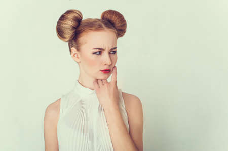 slander: Close-up portrait of offended beautiful girl with funny hairstyle.  Sly and scheming young woman face expression.