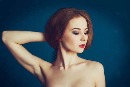 armpits: Close-up portrait beautiful girl on a blue background. Woman showing her armpits