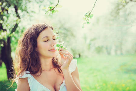 Close-up portrait beautiful girl sniffing flowers apple in the apple orchard Stock Photo
