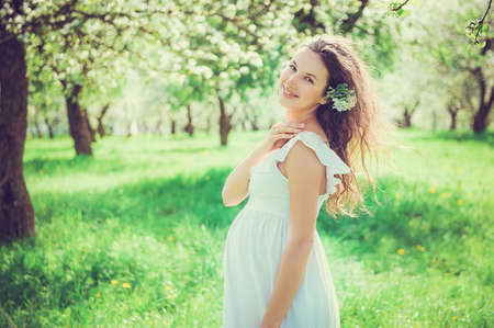 fondling: Pregnant beautiful woman in the apple orchard with a flower in her hair