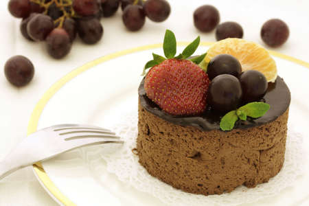 Chocolate cake decorated with strawberry, grape and tangerine slice