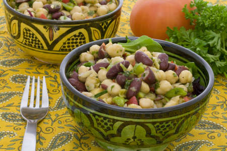 chickpeas and red bean salad served in typical morrocan bowls on a mediterranean tablecloth