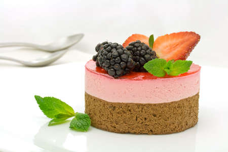 Chocolate and strawberry cake decorated with mulberries and mint leaves