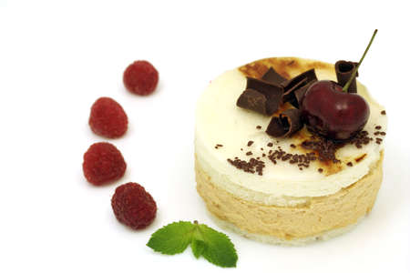 chocolate shavings: Pear mousse cake with cherry, chocolate shavings, decorated with mint leaves and raspberries Stock Photo