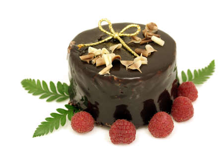 Chocolate cake for Christmas with raspberries and a golden ribbon