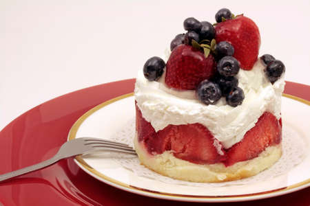 Strawberry and blueberry cheesecake decorated with Chantilly cream and fruits Stock Photo