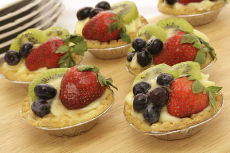 Six summer fruit tartlets on a wooden tray