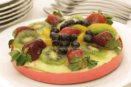 summer fruit custard tart decorated with strawberries, blueberries, kiwi and peach slices Stock Photo