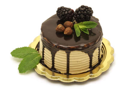 Hazelnut and chocolate mousse cake with mint leaves, on white background