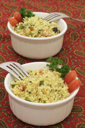 Two ramekins of coucous salad with forks on a colorful tablecloth
