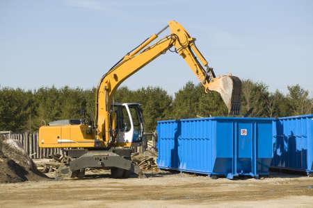 yellow demolition bulldozer beside a dumpster