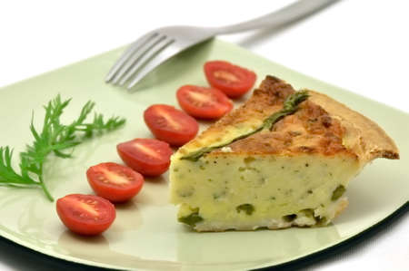 Asparagus quiche slice on a green plate with tomatoes Stock Photo