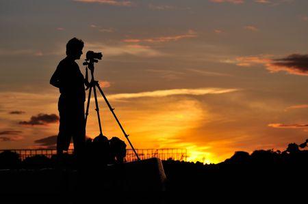 일몰 장면을 촬영하는 사진 작가의 실루엣 스톡 콘텐츠