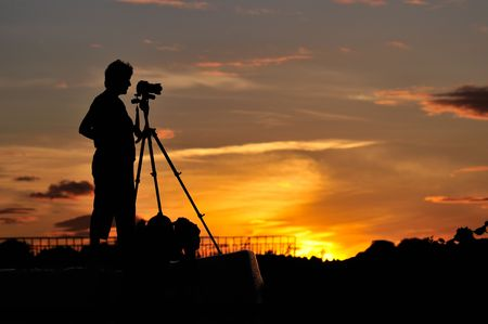 Silueta de un fotógrafo de disparo escena la puesta de sol Foto de archivo