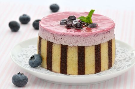 Striped blueberry mousse cake decorated with fruits and mint leaves on a white plate 스톡 콘텐츠