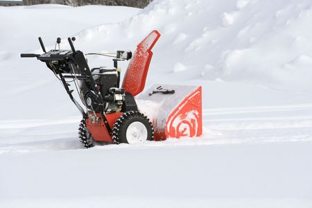 Snow blower in the snow clearing out a path