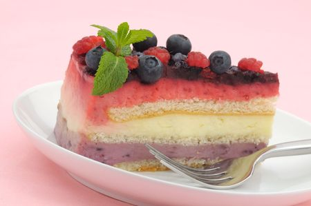 Raspberry and blueberry layer cake slice decorated with mint leaves and fruits