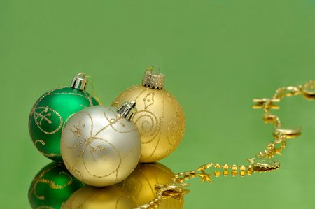 Green and golden baubles and garland on glossy paper Stok Fotoğraf
