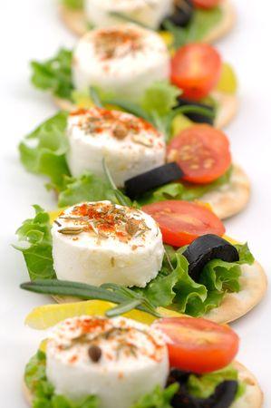 サラダ葉、トマト、オリーブ、スパイスとクラッカーの上の小さいヤギのチーズのスライス 写真素材