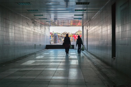 Mother and son walk to the light in the end of the tunnel.