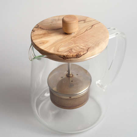 Empty glass teapot with wooden cap on light background