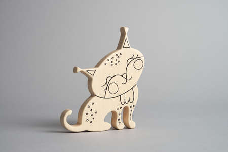 The wooden toy of lynx for kids front view isolated light background at the studio. Smiling animal