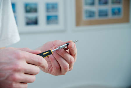 Man holds a screwdriver in his hands - white skin, black and yellow screwdriver Stock Photo