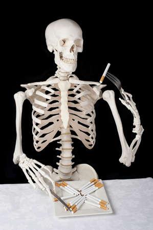 malos habitos: Un esqueleto se come los cigarrillos de una placa, con un cuchillo y un tenedor.