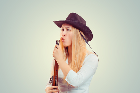 Modern blond woman in cowboy hat holding gun and blowing at it after shooting