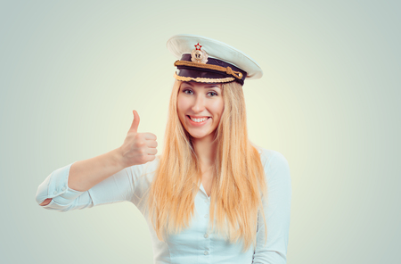 Happy blond woman wearing white shirt and navy service cap showing thumb up and smiling