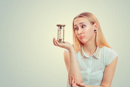 Femme blonde faisant l'expression du visage de pitié et regardant le sablier dans l'espoir Banque d'images