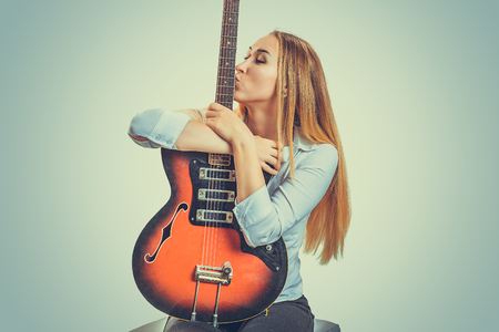 Young devoted woman sitting on gray background and kissing electric guitar Archivio Fotografico