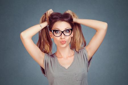 Schönheitsfrau, die an den Haaren hält, die Grimasse im Gesicht zeigen, verzogene Lippen, die Kuss auf grauem grauem Studio lokalisiert durchbrennen Horizontale Wandhintergrund. Positiver Gesichtsausdruck, menschliche Emotionen, Körpersprache.