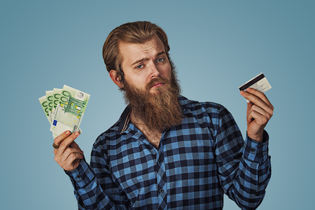 Businessman skeptical choosing holding showing plastic credit card or money cash euro banknotes bills Bearded hipster business man Isolated on blue Background. Negative face expression, human emotion. Imagens