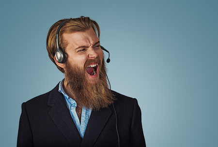 Young adult hipster man with headset working as operator annoyed, frustrated shouting with anger, crazy and yelling, angry customer service representative concept on blue Background. Negative face 版權商用圖片