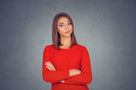 Grumpy skeptical woman Isolated on gray grey studio wall Background. Business woman in red dress, bob hairstyle. Negative face expression human emotion body language reaction attitude. Horizontal shot