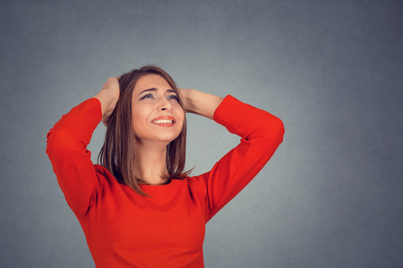 Closeup portrait young angry unhappy stressed woman covering her ears looking up stop making loud noise its giving me headache isolated grey wall background. Negative emotion face expression feeling 写真素材
