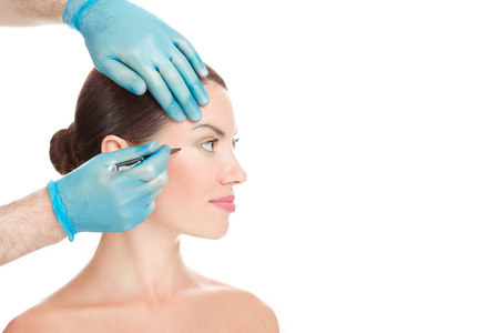 Anti wrinkle procedure. Crow-feet wrinkles reduction removal plastic surgery cosmetic filling operation concept. Doctor surgeon hand in gloves draw wrinkle line on Woman isolated white background. Banque d'images