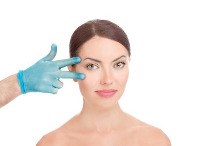 Obere und untere Blepharoplastik. Schöne 39-jährige Frau im mittleren Alter, die sich auf die Augenlidstraffung der plastischen Chirurgie vorbereitet. Die Hände des Arztes in blauen Handschuhen zeigen die Finger auf ihr Auge auf Weiß. Konzept verschönern.