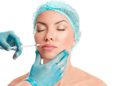 Young beautiful woman getting ready for lips augmentation, plastic surgery, doctors hand in blue gloves injecting hyaluronic acid or botulinum toxin in her lips isolated on white background.