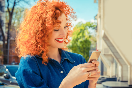 Young beautiful red curly hair woman, smiling, looking her mobile phone texting, reading sms message. Isolated city on background. Positive human emotions face expression feelings.